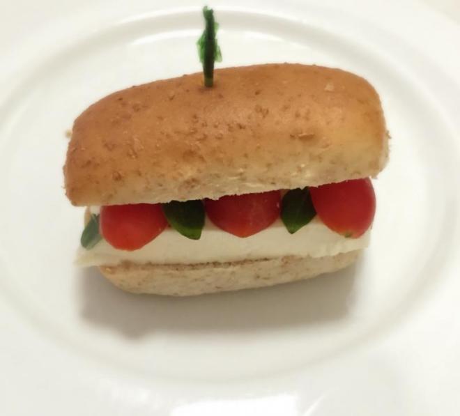 Bisnaguinha integral com queijo branco, tomate cereja e manjericão